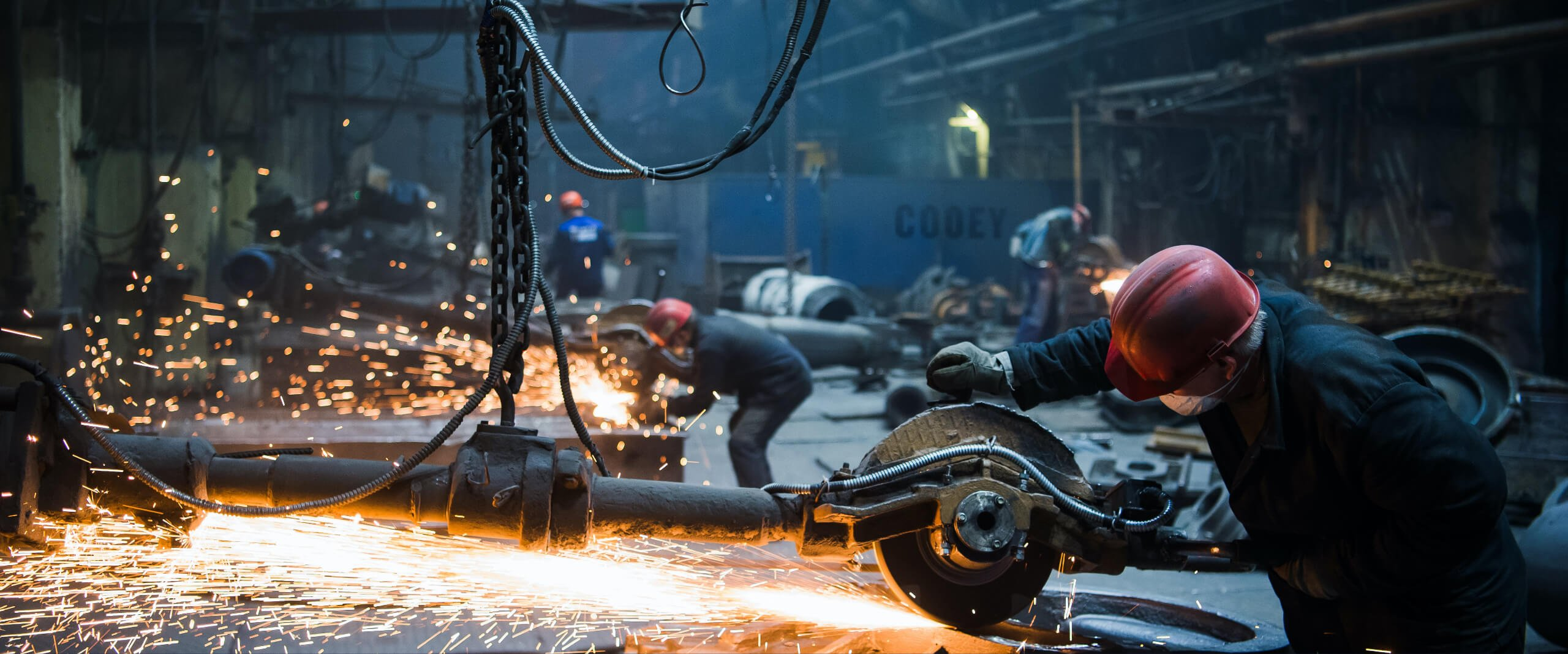 Sparks fly as factory workers cut steel with large saws in factory setting