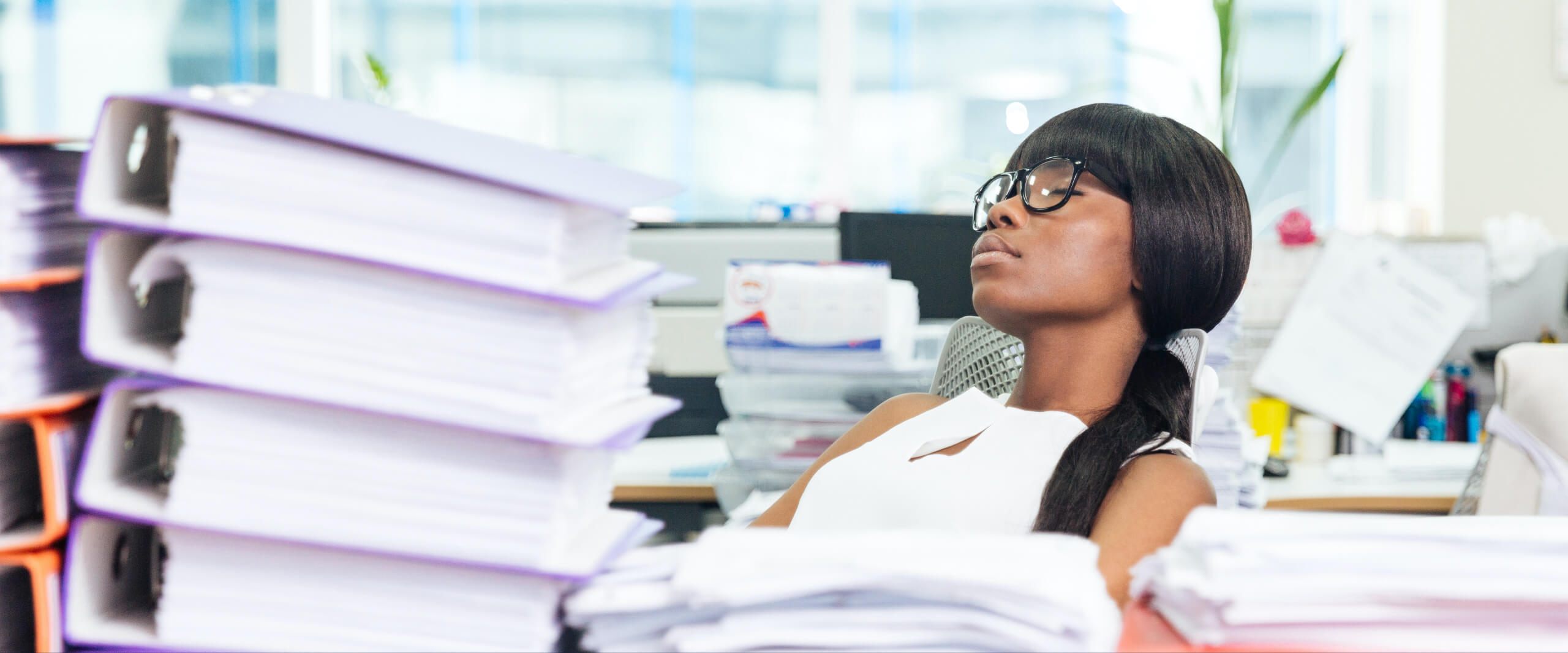 Woman sighing with eyes closed at her desk with an overwhelming amount of binders and paperwork