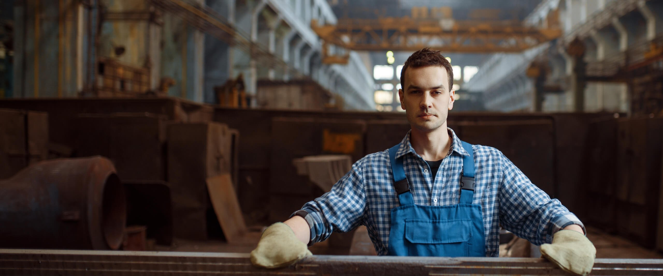 Industrial ship builder wearing blue overalls poses for the camera in a factory setting