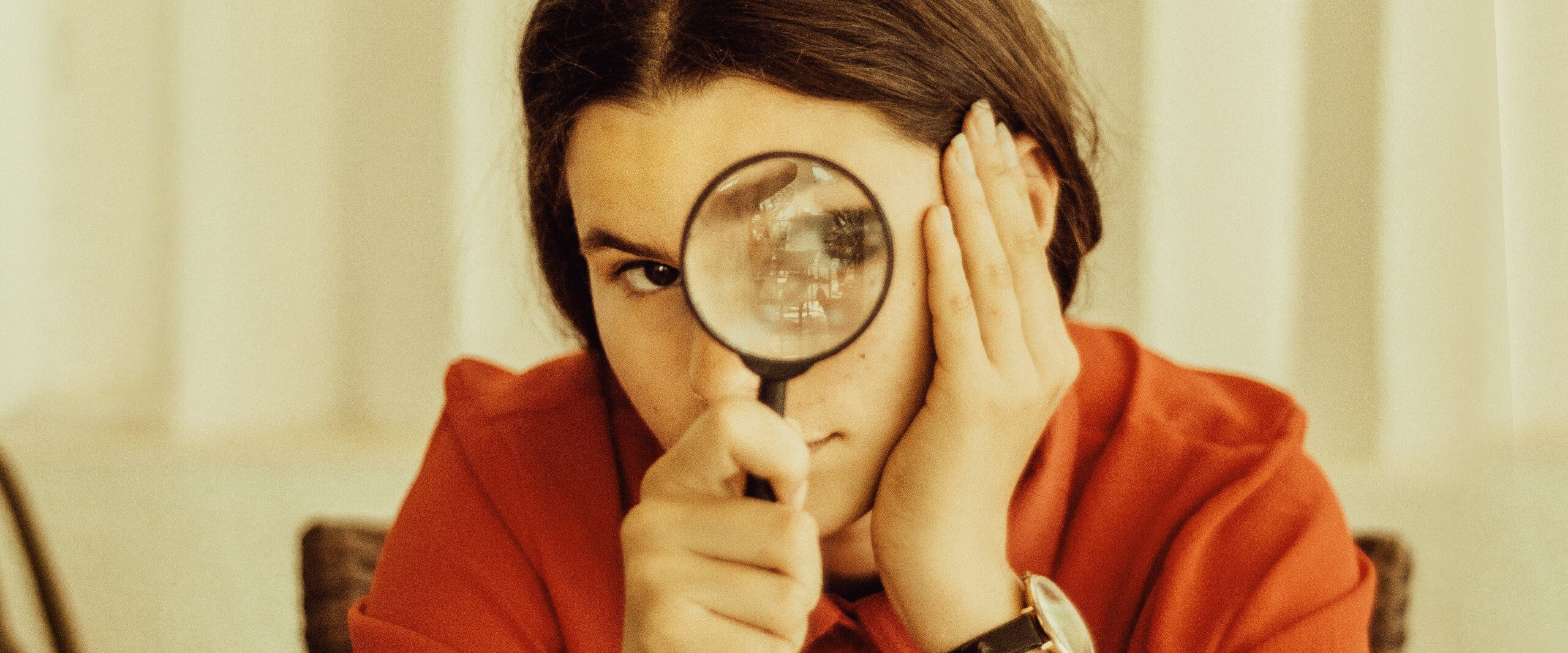 Photo of a woman in an orange shirt looking into the camera with a magnifying glass up to her eye